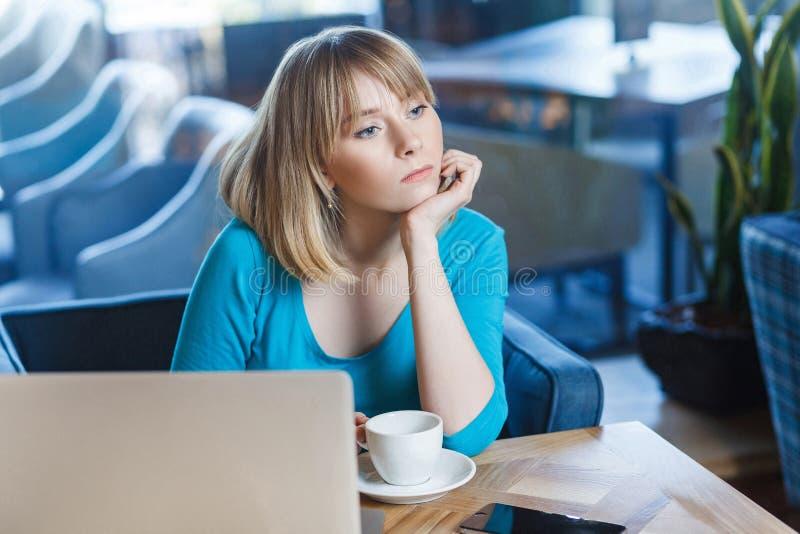 有白肤金发的突然移动理发头发的美丽的thinkful少女自由职业者在蓝色女衬衫在咖啡馆坐并且作梦,有新 免版税图库摄影