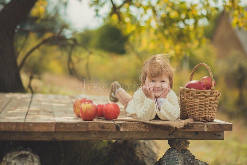 有白肤金发的红色头发佩带的象牙颜色白色毛线衣的可爱的俏丽的女婴在城市木的郊区村庄享受生活时间 库存照片