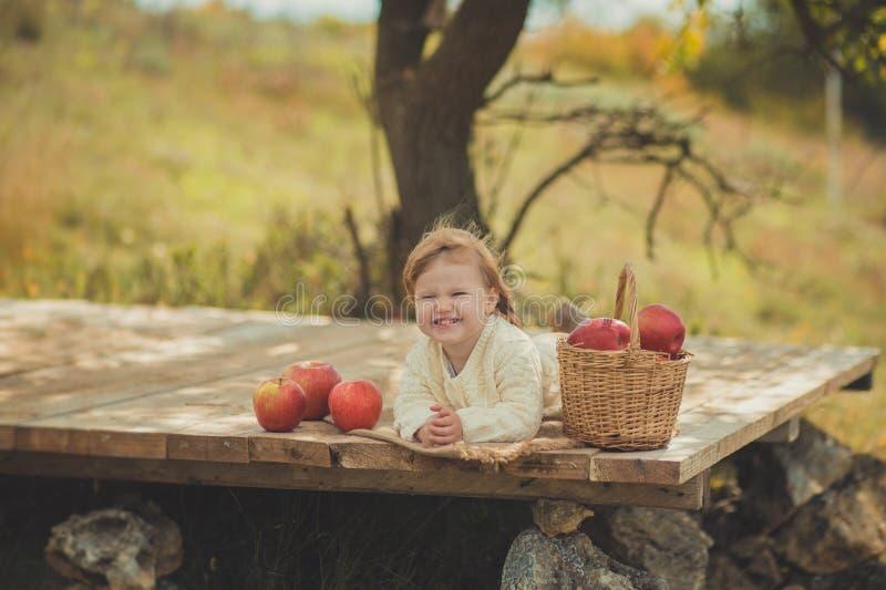 有白肤金发的红色头发佩带的象牙颜色白色毛线衣的可爱的俏丽的女婴在城市木的郊区村庄享受生活时间 图库摄影
