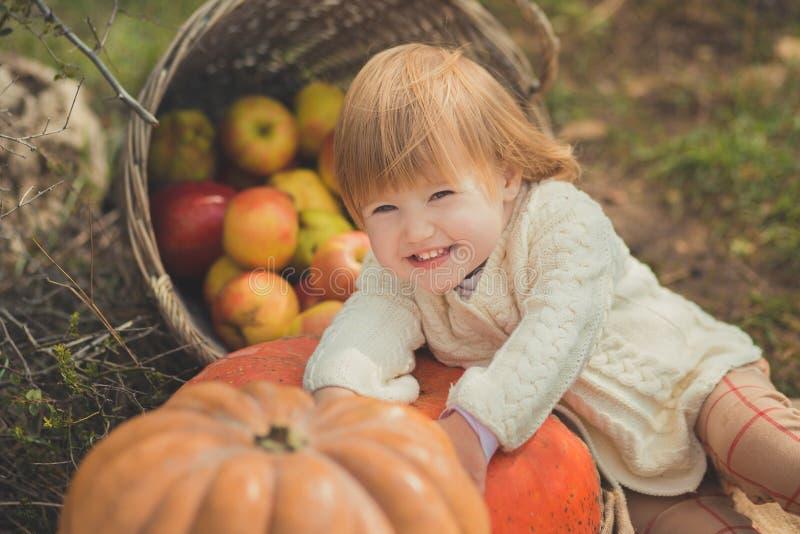 有白肤金发的红色头发佩带的象牙颜色白色毛线衣的接近的画象女婴享用生活时间有篮子ped小儿床的城市村庄 库存照片