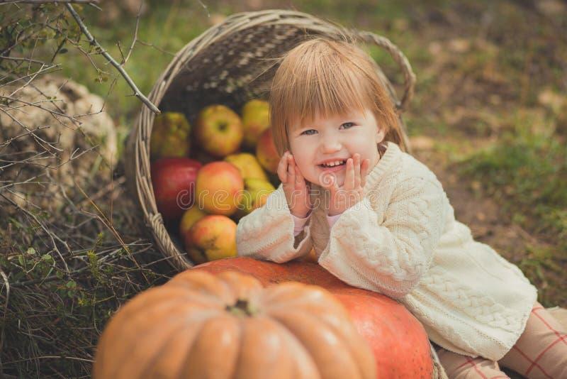 有白肤金发的红色头发佩带的象牙颜色白色毛线衣的接近的画象女婴享用生活时间有篮子ped小儿床的城市村庄 库存图片