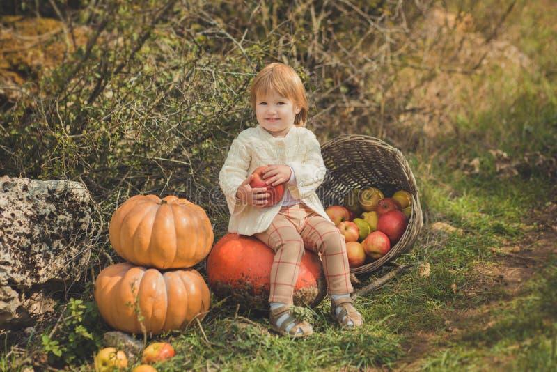 有白肤金发的红色头发佩带的象牙颜色白色毛线衣的接近的画象女婴享用生活时间有篮子ped小儿床的城市村庄 免版税库存图片