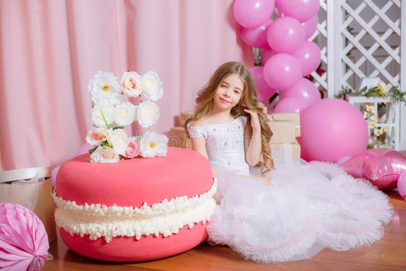 有白肤金发的长的头发的小女孩庆祝与玫瑰色装饰的生日快乐党 库存照片
