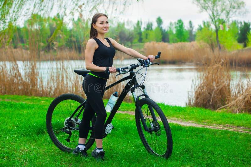 有白肤金发,长的头发的女孩运动员在黑色在公园炫耀贴身衬衣和T恤杉走与自行车的早晨的 免版税库存照片