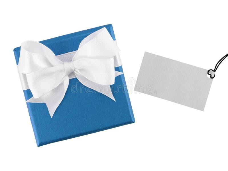 有白色丝带弓的蓝色礼物盒和写的被隔绝的消息空白的灰色贺卡在白色背景 免版税库存照片