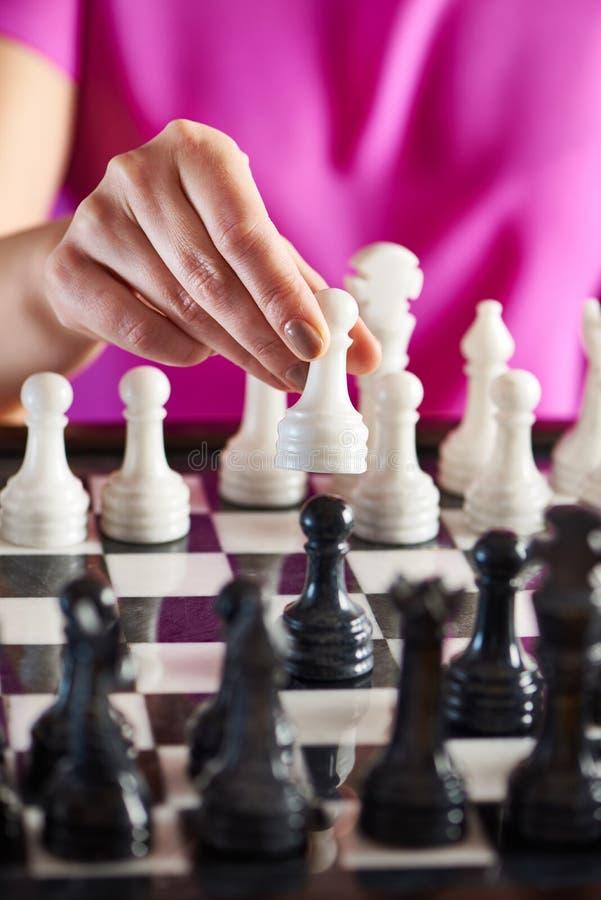 有白色典当的手在棋枰 免版税库存图片