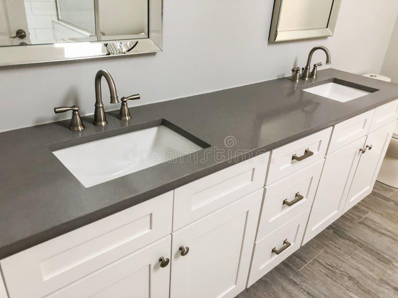 有白色内阁和石英工作台面的现代卫生间,两个水槽和龙头有石地板的 免版税库存照片