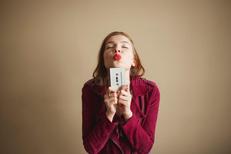 有白色减速火箭的卡型盒式录音机的年轻行家妇女 ?90s?? 免版税库存照片