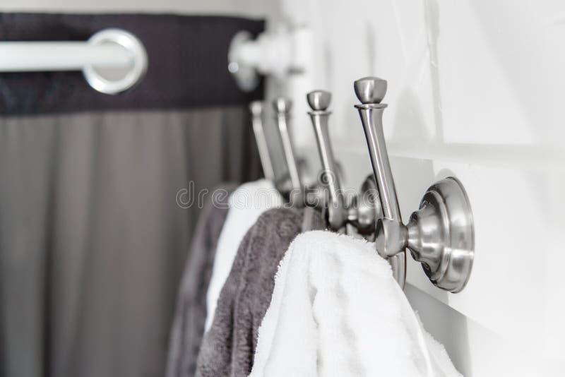 有白色和灰色毛巾的银色金属勾子 库存图片