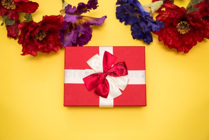 有白色和红色弓的真正的在黄色背景用不同的花顶视图的箱子和丝带在情人节隔绝的 平面 免版税图库摄影