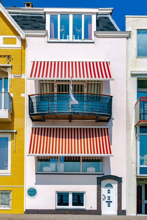 有白色和红色镶边太阳窗帘的一个美丽的白海手段房子 E ?? 免版税图库摄影
