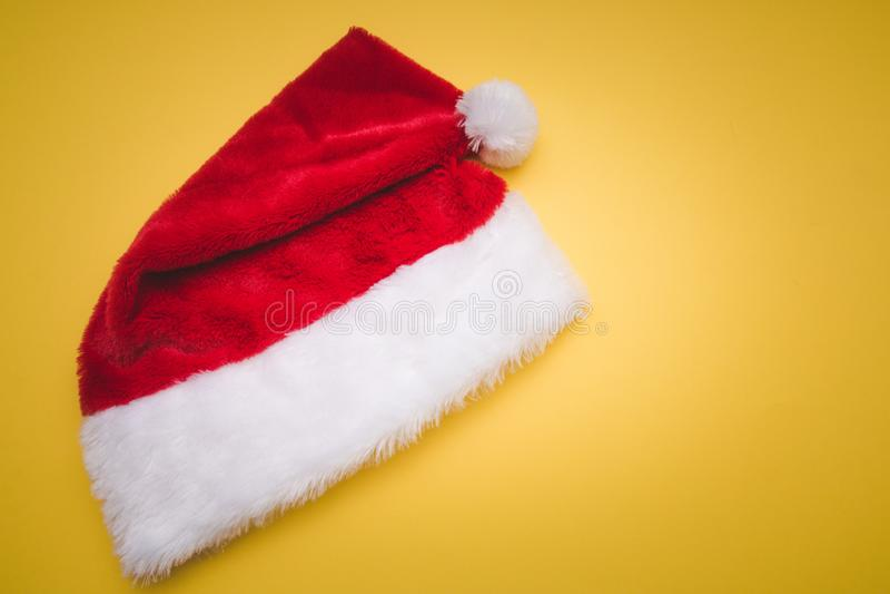 有白色大型机关炮黄色的圣诞节红色圣诞老人项目帽子 背景对光检查被设色的装饰下落玻璃金子图象沙子 免版税图库摄影