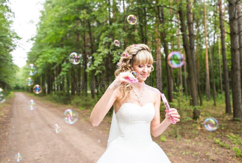 有白色婚礼礼服吹的泡影的美丽的少妇户外 免版税库存图片