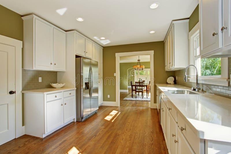 有白色存贮组合的绿色厨房室 免版税库存照片