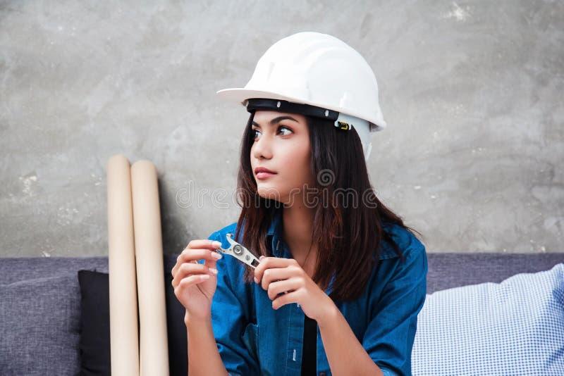 有白色安全帽的年轻女性建筑师,坐沙发和看背景的右边 免版税库存照片