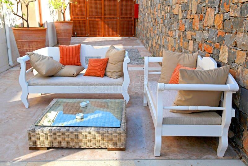 有白色室外家具的美丽的地中海露台 免版税库存图片
