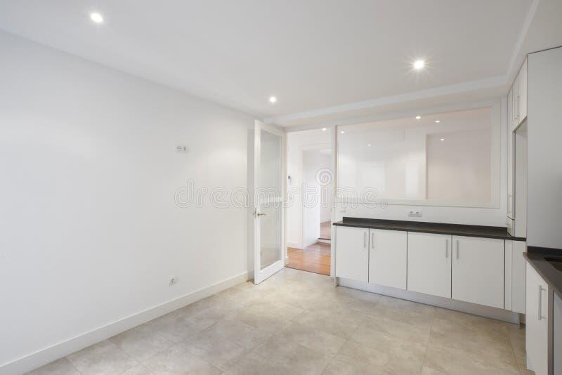 有白色家具的空的房子厨房 免版税库存照片