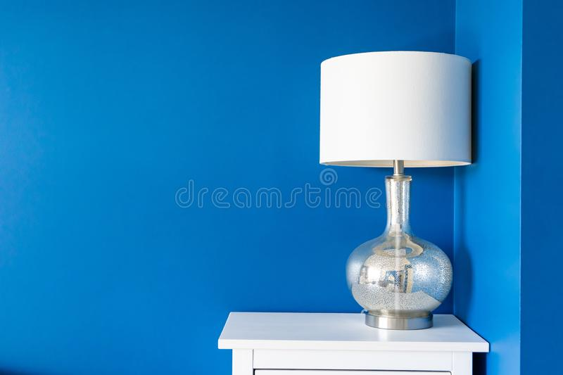 有白色家庭装饰的充满活力的蓝色被绘的墙壁在一张不眠夜桌重读一个白色灯罩和银色金属灯立场, 库存照片