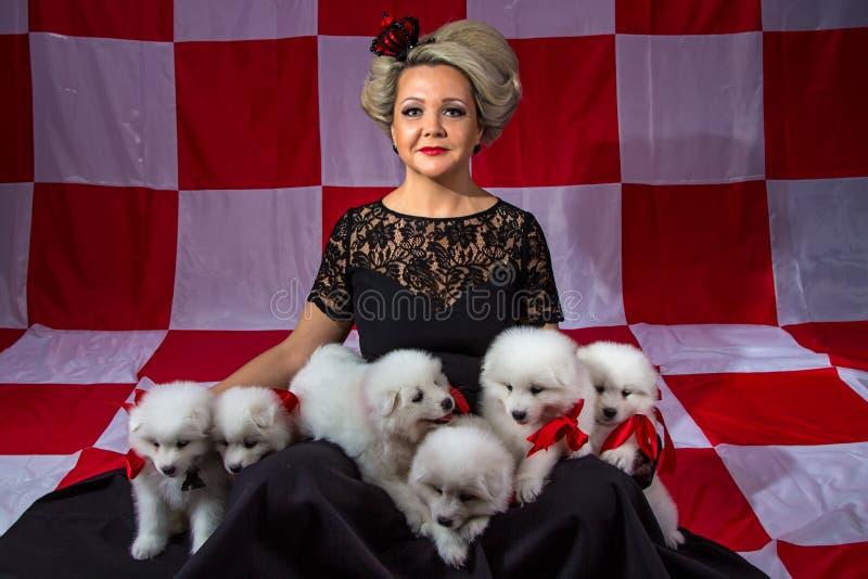 有白色小的小狗的愉快的妇女 免版税库存图片