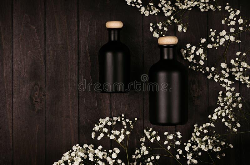 有白色小花的空白的黑化妆用品瓶在黑暗的木委员会,嘲笑,顶视图 免版税库存照片