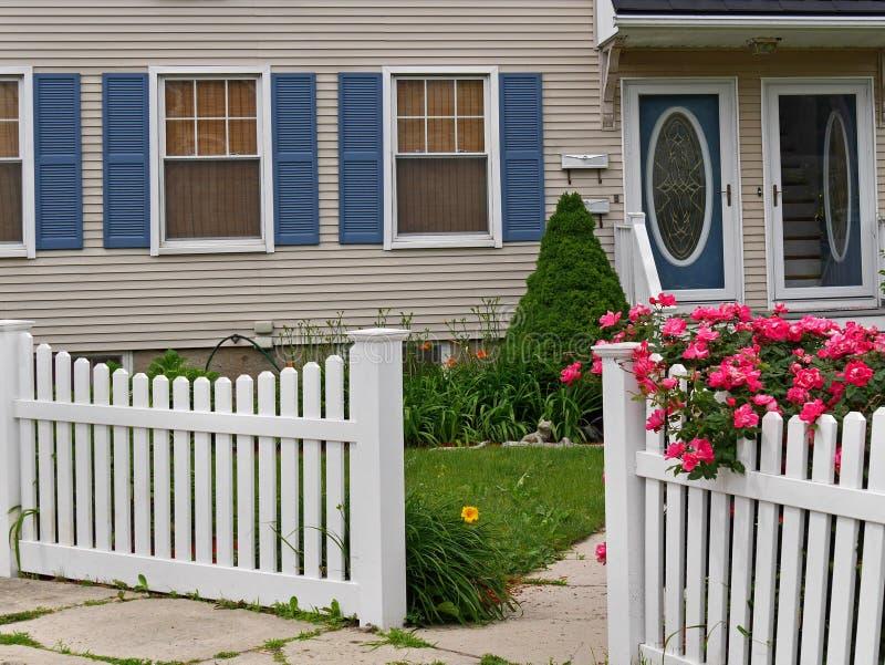 有白色尖桩篱栅的前院 免版税库存照片