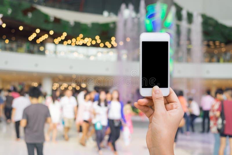有白色屏幕的巧妙的电话在手中在弄脏在购物的mal 免版税库存图片