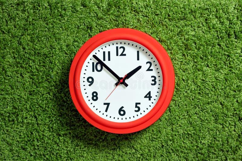 有白色拨号盘的红色时钟在绿色地毯 库存照片