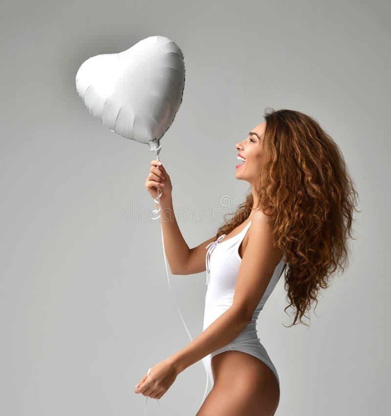 有白色星气球的年轻愉快的女孩作为birthd的一个礼物 库存照片