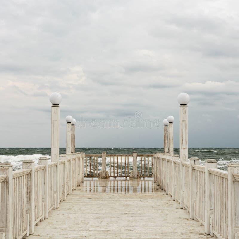 有白色木扶手栏杆的码头海上在风暴期间的 免版税库存图片