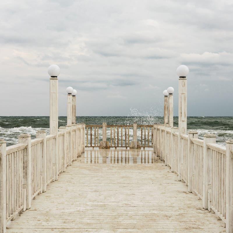 有白色木扶手栏杆的码头海上在风暴期间的 免版税库存照片