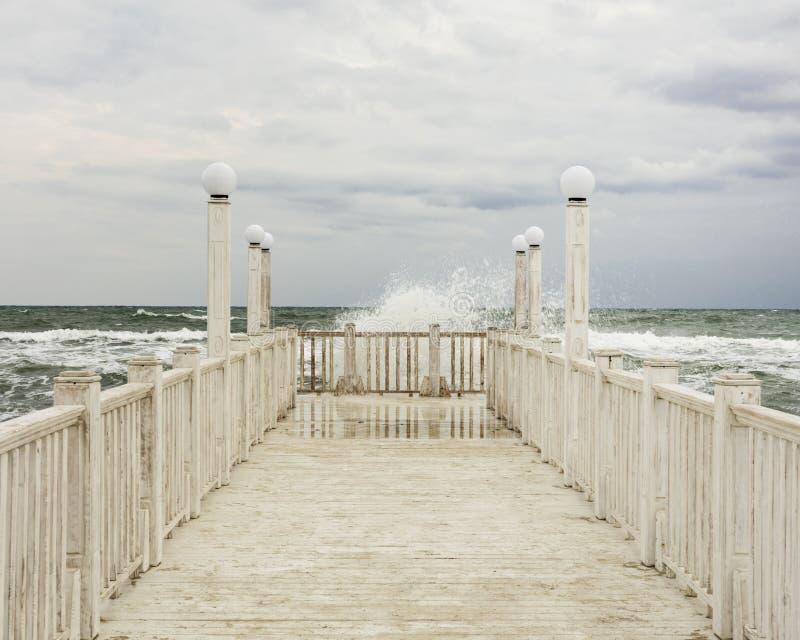 有白色木扶手栏杆的码头海上在风暴期间的 图库摄影