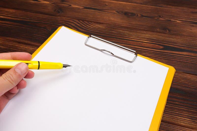 有白色板料的剪贴板在木背景 顶视图 库存图片