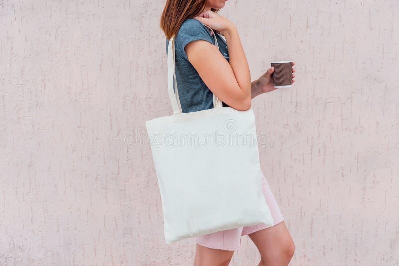 有白色棉花袋子的年轻女人和纸咖啡杯在她的手上 免版税库存照片