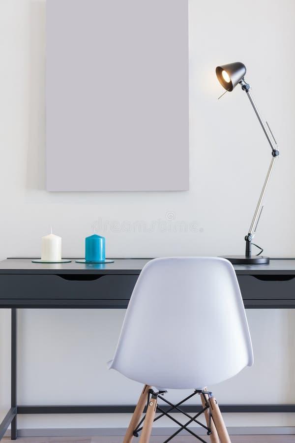 有白色椅子和唯一灯的小办公桌 库存图片