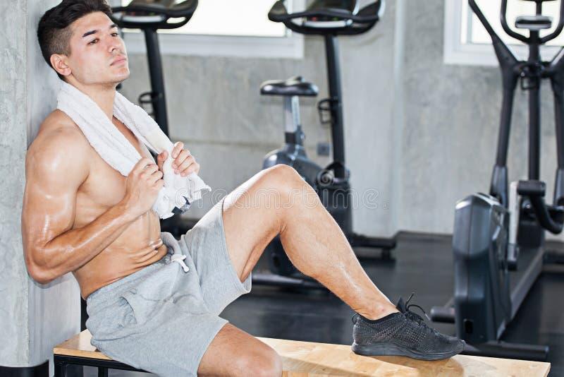 有白色毛巾的英俊的肌肉爱好健美者人坐a 免版税库存图片