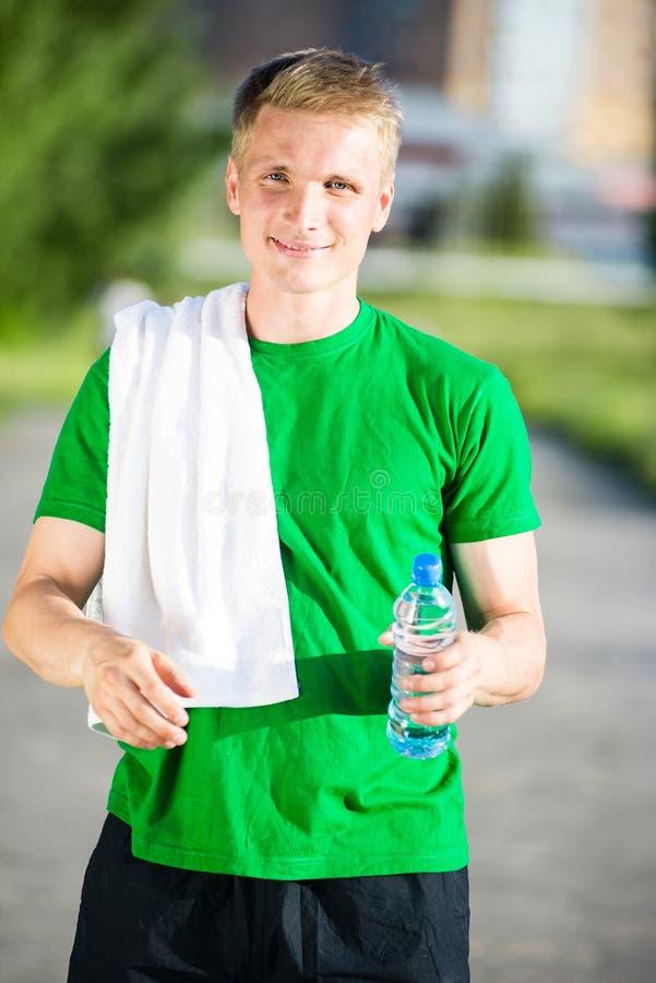 有白色毛巾饮用水的疲乏的人从塑料瓶 免版税库存图片