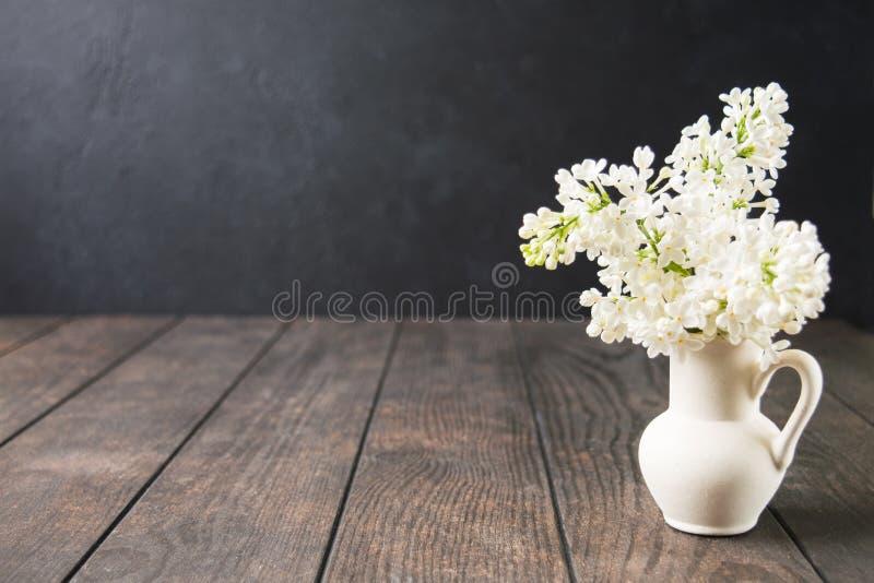 有白色淡紫色花的白色陶瓷花瓶在木桌上 温泉春天或夏天芳香疗法概念 ?? r 图库摄影