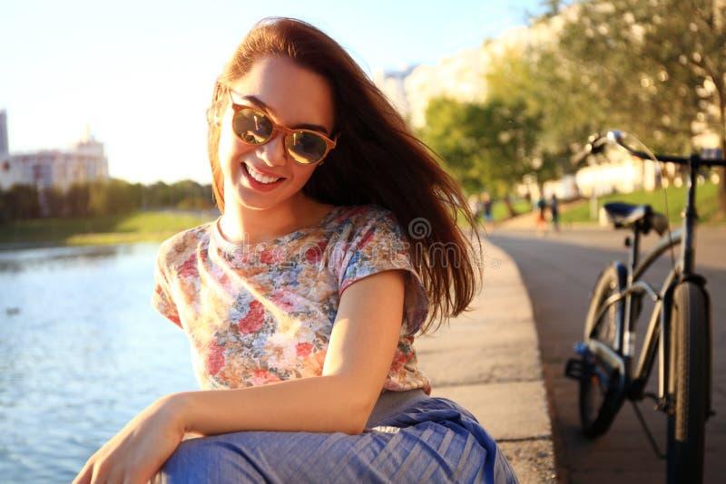 有白色牙的妇女认为和看斜向一边在一个公园的在夏天 库存图片