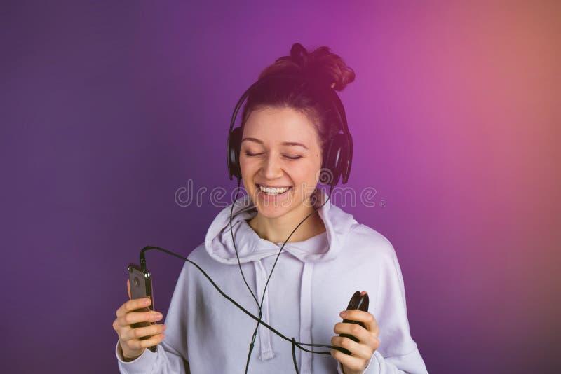 有白色牙的微笑的年轻美丽的女孩听到在电话佩带的耳机的音乐的在a的一件运动衫 免版税库存照片