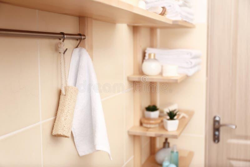 有白色特里毛巾的机架和丝瓜络在卫生间里 免版税图库摄影