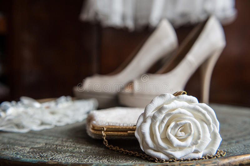 有白色玫瑰、鞋子和袜带的妇女的传动器在有装饰品的黄铜盘子 库存照片