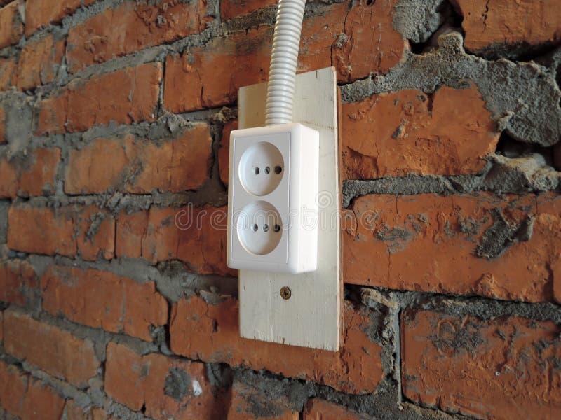 有白色电子插座插口的红砖墙壁在车库 图库摄影