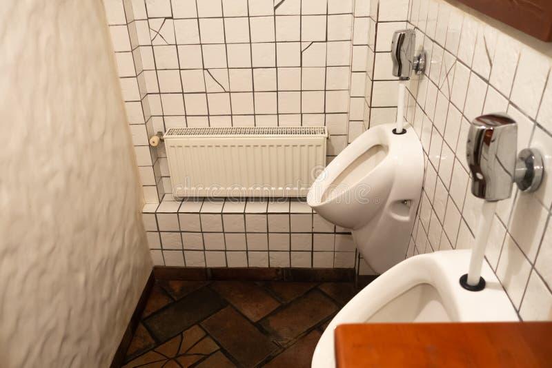 有白色男性马桶的干净和卫生学卫生间在男性洗手间室,wc 图库摄影