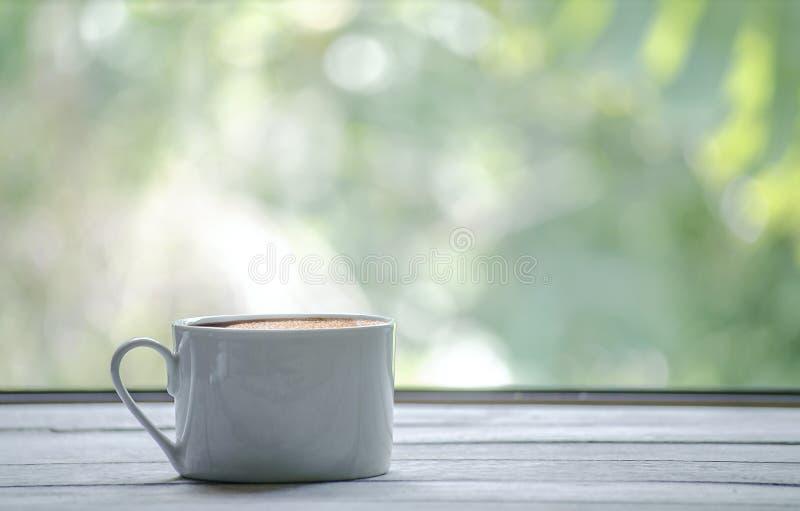 有白色的热的咖啡杯木桌和绿色叶子背景与拷贝空间在右边 免版税库存图片