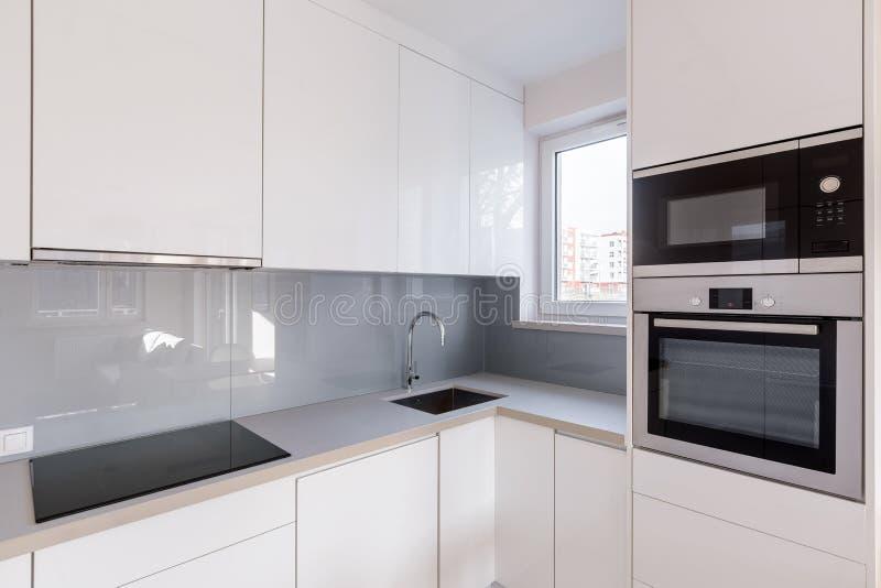 有白色碗柜的现代厨房 免版税库存图片