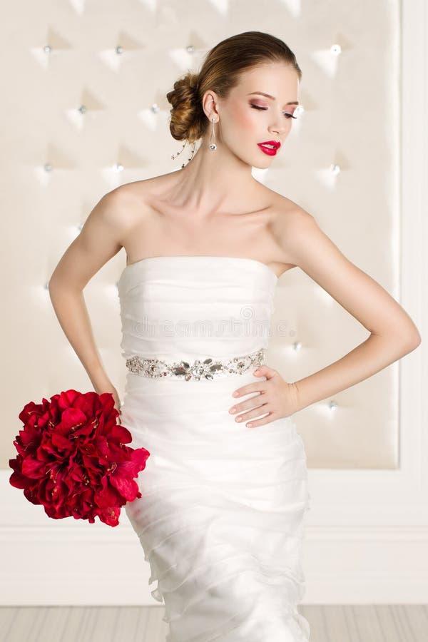 有白色礼服的华美的新娘有红色的开花花束 库存图片