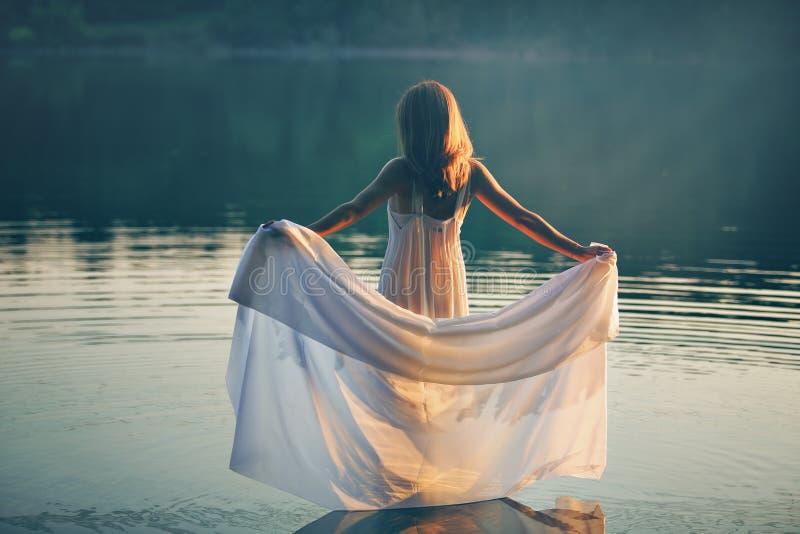 有白色礼服的妇女在日落的一个湖 免版税库存图片
