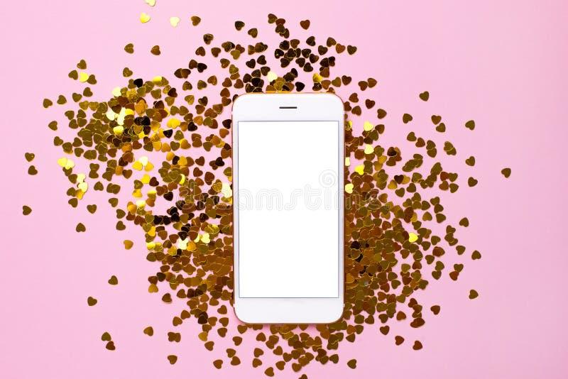 有白色空的屏幕的手机在粉色与金黄心脏五彩纸屑的纸背景 免版税库存照片