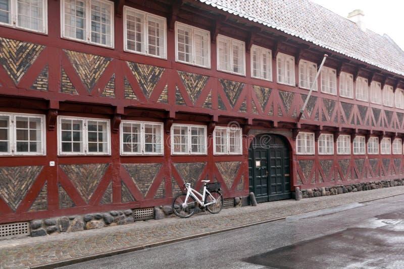 有白色窗口的红色老房子-半木料半灰泥的房子由木头和砖做成 自行车在墙壁附近的哥本哈根丹麦 库存照片
