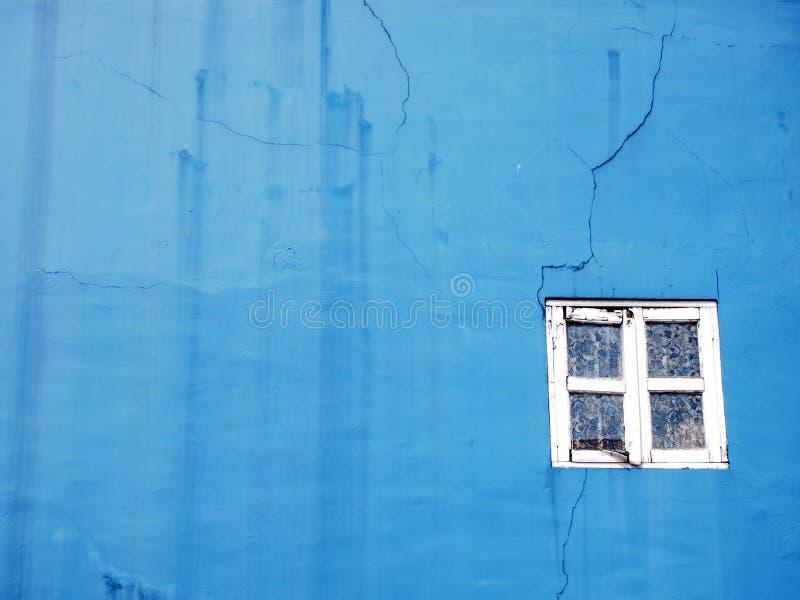 有白色窗架的蓝色墙壁 免版税库存图片